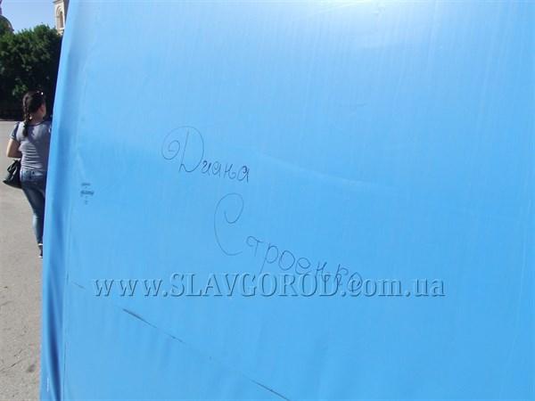 На новом тенте сцены на центральной площади Славянска появились дырки и надписи