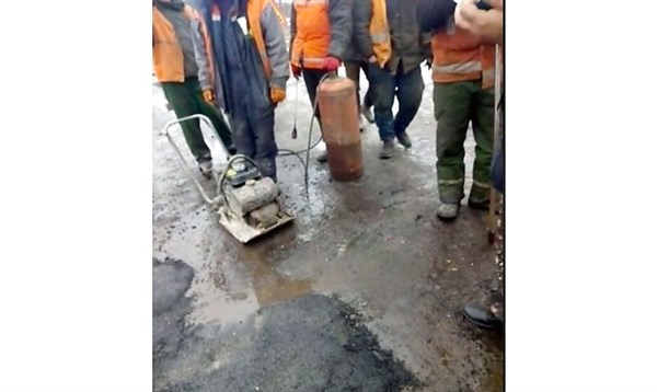 В Славянске кладут асфальт на мокрую дорогу, покрытую лужами. Это называется ямочный ремонт